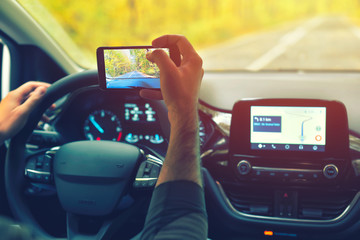 Male driver using smartphone to capture pictures of road, while driving