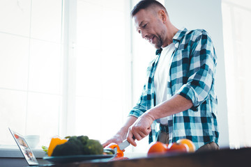 Man in the kitchen. Pleasant adult man developing his cooking skills while being in the kitchen