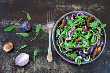 Fresh salad in a bowl. Vegan salad with arugula, plum and blue onion.