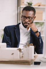 pensive african american architect working with business buildings model