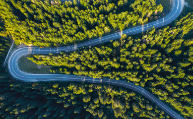 Aerial view of winding road in green forest
