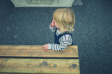 Toddler standing by a bench