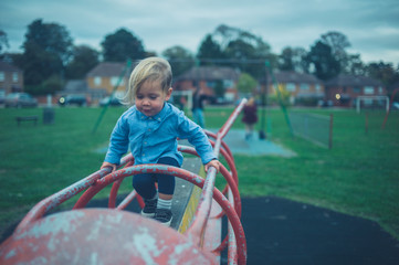 Toddler on play equipment in the park