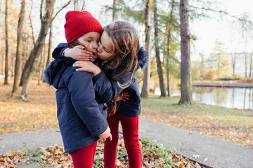 Two happy children hugging and kissing in autumn park. Close up sunny lifestyle fashion portrait of two beautiful caucasian girls outdoors, wearing cute trendy outfit. Sisters relationship