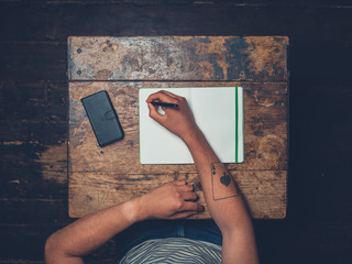 Overhead shot of man writing in notebook
