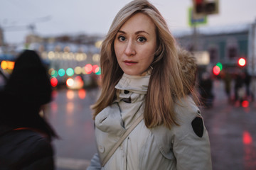 Beautiful young woman with big eyes and long blond hair in jacket with hood stands on evening city street.