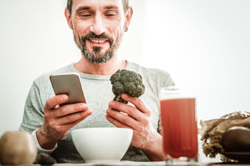 Favourite vegetable. Cheerful happy man looking at the broccoli while holding a smartphone in his hands