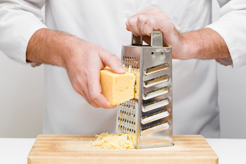 Chef's hands grating piece of cheese with steel grater on the wooden board in professional kitchen. Preparing for italian pizza, lasagna or snack. Front view.