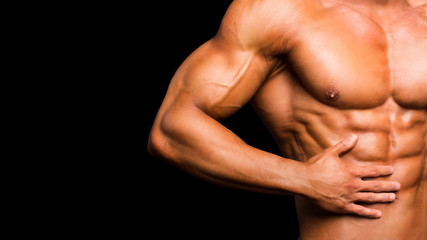 Fitness concept. Muscular and fit torso of young man having perfect abs, bicep and chest. Male hunk with athletic body on black background.
