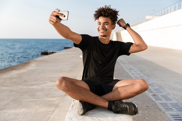 Happy young african sportsman at the beach