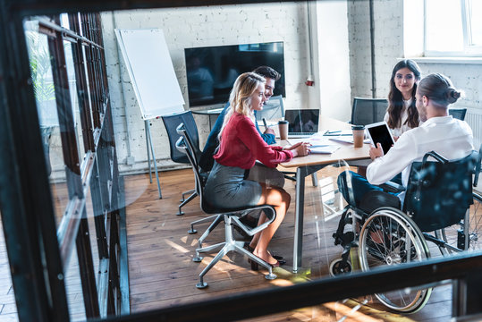 young handicapped businessman in wheelchair working with colleagues in office