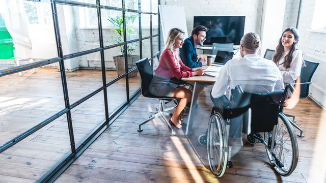 young disabled businessman in wheelchair working with smiling colleagues in office
