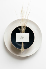 Table setting with a white plate and a black bowl styled with dried grass and a handwritten place card.