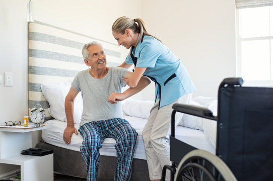 Nurse helping old patient get up
