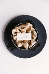 A handwritten place card on a bed of silk ribbon as part of a wedding table setting.
