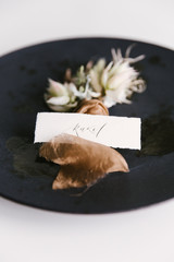 Two floral corsages lying on a plate with a handwritten place card.