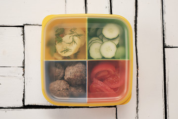 Cooked lunch in a separate container. Boiled potatoes, cucumbers, tomatoes and steak patties.