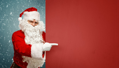 Happy Santa Claus points to a blank banner with to copy space.