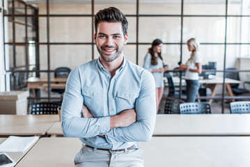 handsome young businessman with crossed arms smiling at camera in office