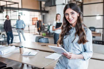 beautiful young businesswoman using digital tablet and smiling at camera in office
