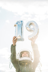 Beautiful woman poses with number 19 dressed as an astronaut.