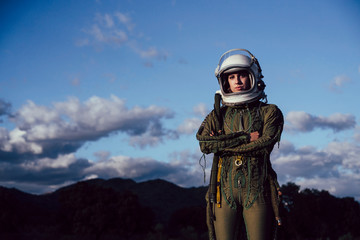 Beautiful woman poses looking at camera dressed as an astronaut.