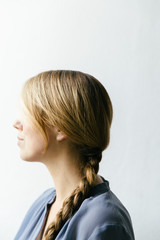 A woman with long dark blond hair tied up in a braid looking towards the light seen en profil from the side.