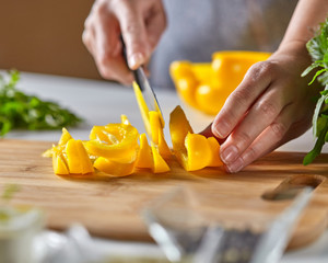 Juicy slices of yellow pepper cut a woman's hands into a wooden board on a white kitchen table with tomatoes and parsley. Copy space for text. Step by Step Cooking Healthy Salad