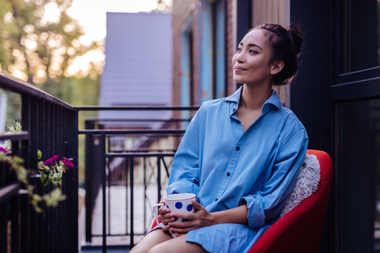 From the balcony. Joyful Asian woman looking at the street while holding a cup of tea