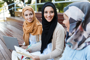 Friends muslim sisters women sitting outdoors using laptop computers.