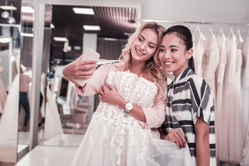 Great photo. Happy positive women taking a selfie together while being in the wedding boutique