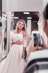 With a wedding dress. Nice beautiful woman holding a wedding dress while having her photo taken