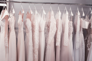 New collection. Close up of beautiful wedding dresses hanging in the shop