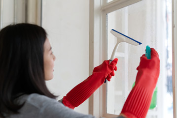 Side view of young Asian girl wearing in grey shirt and red protective gloves with glass cleaning equipment, cleaning window at home with smile. Happy cleaning service concept.