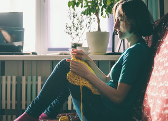 Girl knits crochet at home.