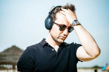 Fashionable man wearing sunglasses enjoying music on his headphones