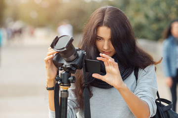 Woman professional photographer taking landscape images with dslr camera and tripod outdoors. Gorgeous mixed race Asian Caucasian female enjoying traveling outdoors during holidays in Europe.