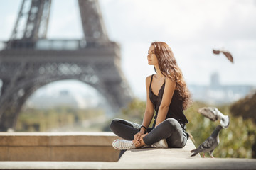 Happy travel woman near the Eiffel tower, Paris. Travel tourist girl on vacation resting happy outdoors. Pigeons symbol of love flying around fliynig Attractive young romantic woman sitting against Fototapete