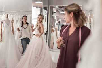 In the wedding boutique. Joyful young women looking at the wedding dress designer while being in the wedding shop