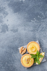 Homemade lemon curd in tartlets with fresh lemon and mint leaves. Copy space