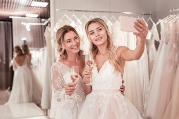Beautiful photo. Joyful positive brides holding glasses with sparkling wine while taking a selfie together