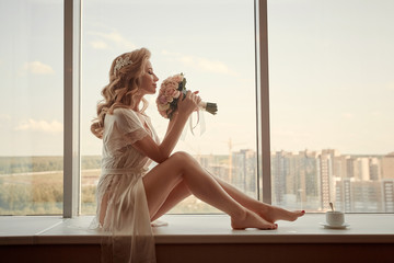 Portrait of a young beautiful girl bride. Sits on the window with a bouquet. Wedding preparations