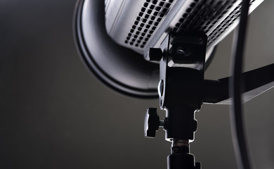 Close-up - place of attachment to the rack and the body of a professional black studio illuminator. Studio equipment concept