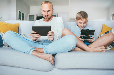 Father and son emotionally playing with electronic devices : tablet and gamepad sitting in living room