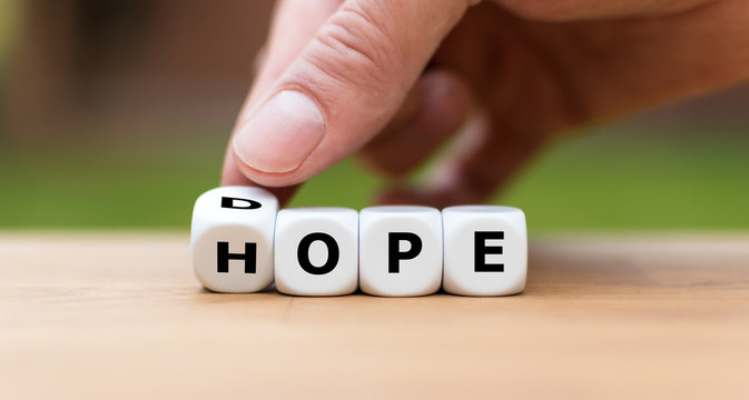 Hand is turning a dice as symbol to have hope instead of dope