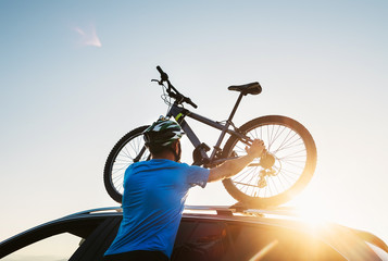 Mountain biker man takes of his bike from the car roof