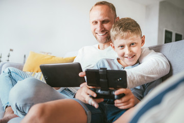 Father and son portrait with electronic devices playing. Sitting at home in cozy atmosphere