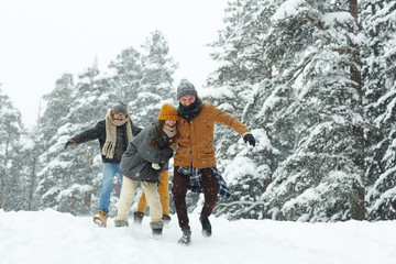 Positive excited young friends in warm clothing running over winter hill while having fun in forest