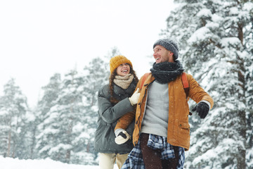 Jolly beautiful young couple in puffy jackets holding hands and laughing while enjoying winter stroll, hiking in forest
