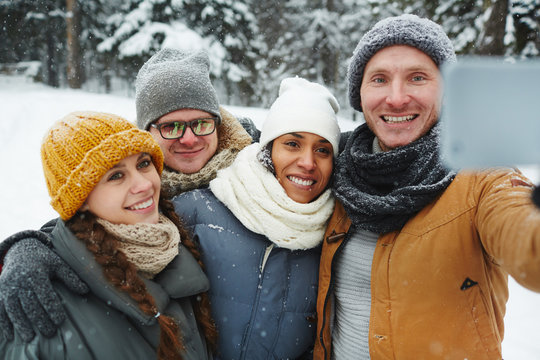 Positive excited young friends in warm hats and scarves posing for selfie and embracing in winter park